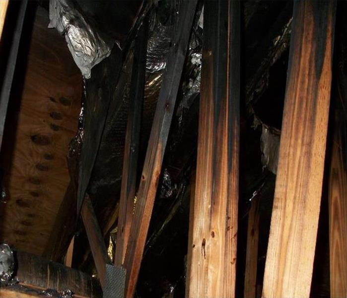 exposed rafters, burnt black in areas