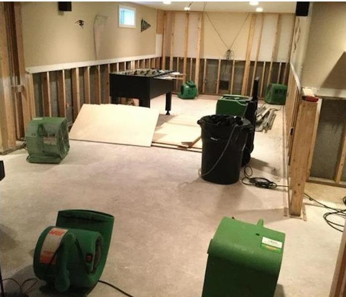 carpet removed, lower wall panels removed, studs showing, equipment drying out the room