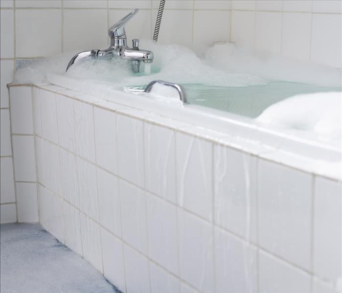 Tub overflowing with soapy water from an open tap