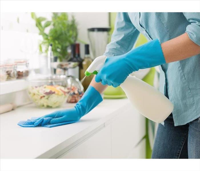 Blue gloved hands spraying a countertop and wiping with a blue rag